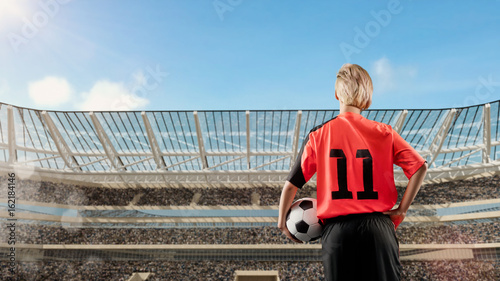 female soccer player standing with the ball against the crowded stadium on background