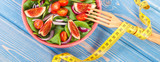 Fruit and vegetable salad and fork with tape measure on blue boards, healthy nutrition concept © ratmaner