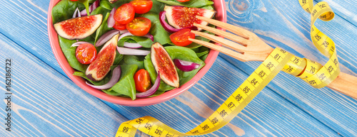 Fruit and vegetable salad and fork with tape measure on blue boards, healthy nutrition concept