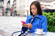 Cafe woman texting sms on phone app drinking cappuccino coffee at outdoor street terrasse in european city. Europe travel lifestyle. Asian businesswoman in blue trench coat.