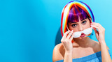 Fototapety Beautiful woman in a colorful wig on a blue background