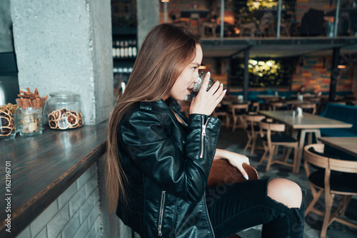 Beautiful girl in a black jacket in a cafe Poster