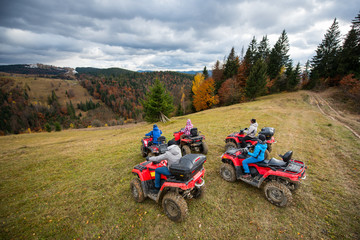 Friends driving quad bikes on the hillside at the background of autumn forest with colorful trees and mountains. Top view