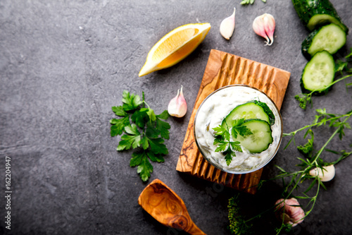 Tzatziki Traditional Greek sauce with ingredients cucumber, garlic, parsley, lemon, mint. Food Background.Snack, Meze in a glass cup.Copy space for Text.selective focus.