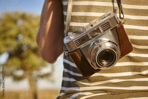 Tourist with vintage camera in the countryside Poster