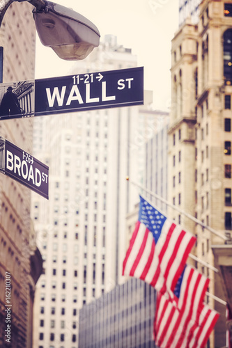Wall Street and Broad Street signs with American flag in distance, shallow depth of field, color toning applied, New York City, USA Poster