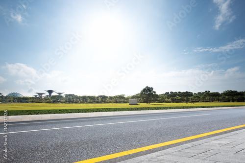 empty road near grassland with blue sky