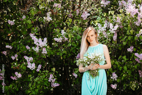 Blonde girl with bouquet of wild flowers outdoors A model in a turquoise dress against a background of a lilac bush.