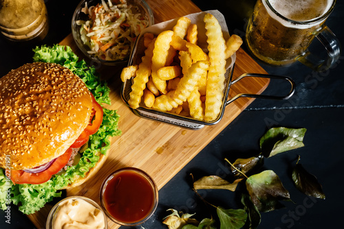 Close up, top view of freshly made beef burger with french fries and beer