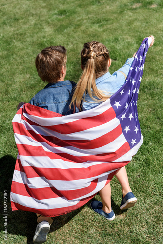 adorable siblings with american flag having fun outdoors, America's Independence Day concept