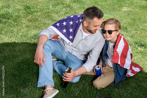 father and son sitting on grass with us flag and holding beer and soda, America's Independence Day concept
