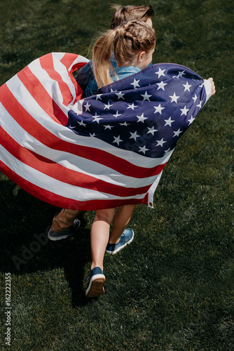 adorable siblings holding american flag and running outdoors, celebrating 4th july - Independence Day