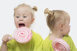 Quadro Small girls twins eat candy on a white background. Two little girls twins have fun eating large round marshmallows on a stick