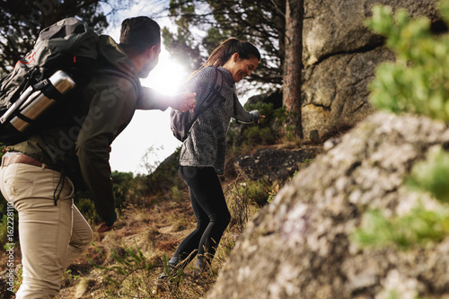 Happy young couple hiking together in mountain Poster
