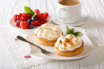 Lemon tart with meringue and berry mix, coffee  close-up. horizontal