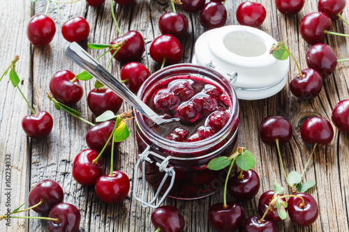 Homemade black cherry jam in the jar on wooden background,selective focus