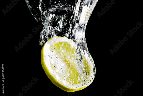 A slice of yellow lemon falls into the water - 162236378