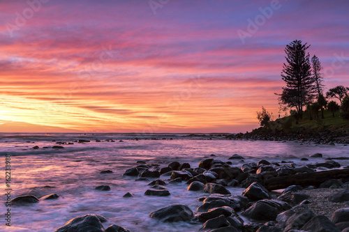 Colourful red and yellow sunrise colours in the clouds at Burleigh Heads Gold Coast.