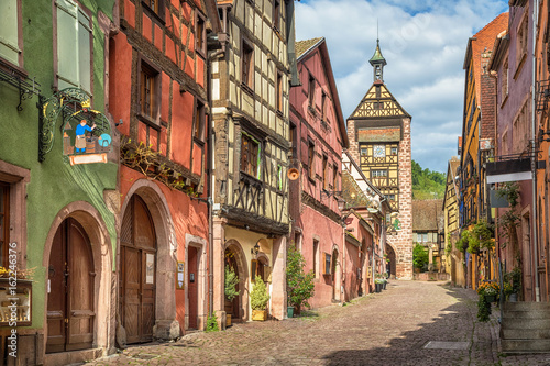 Fototapeta Central street of Riquewihr village with colorful traditional half-timbered french houses and Dolder Tower, Alsace, France