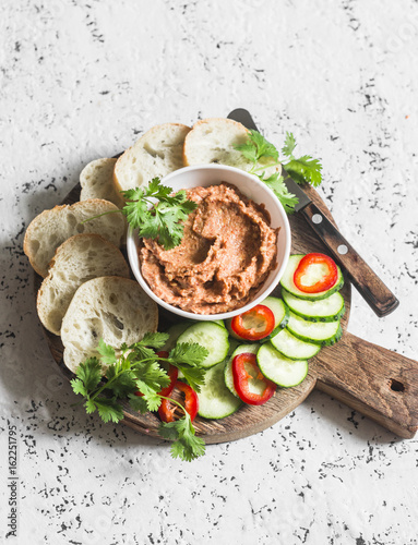 Eggplant, smoked paprika, walnuts dip, vegetables and bread on wooden cutting board on a light background. Vegetarian snack