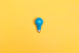 Fototapety Blue painted light bulb on a vibrant background