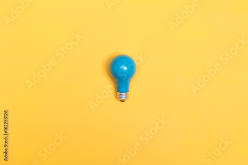 Foto Murales Blue painted light bulb on a vibrant background