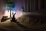 Toy rabbit back lit by Tiffany lamp in bedroom. - 162253785