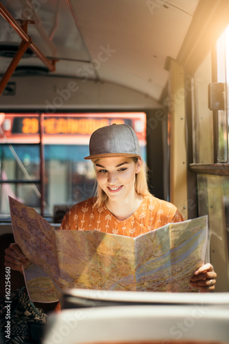 Young teenage girl traveling and using map for orientation in public transportat Poster