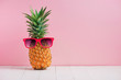Funny pineapple in a sunglasses on table over pink background