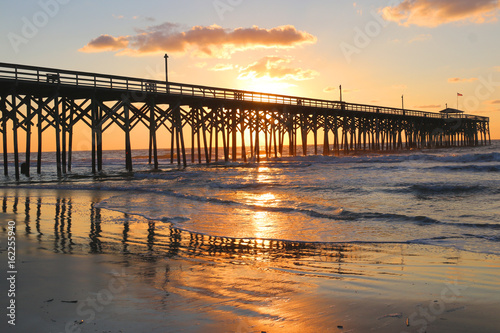 Papiers peints Morning Glory Sunrise at a South Carolina Atlantic coast, Myrtle Beach area, USA. Landscape with the reflection of the sun in shallow water on the foreground and a wooden pier on the background.Vacation background.