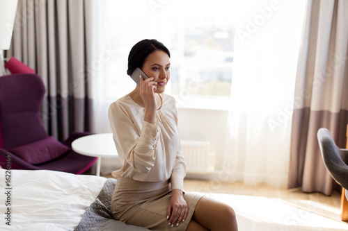 businesswoman with smartphone at hotel room