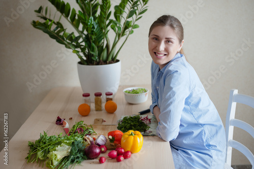 The girl is a vegetarian sits at the kitchen table and smiles. In the foreground are fresh vegetables