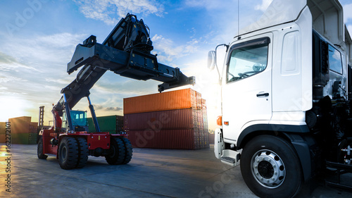 Lift stacker and truck in container depot.