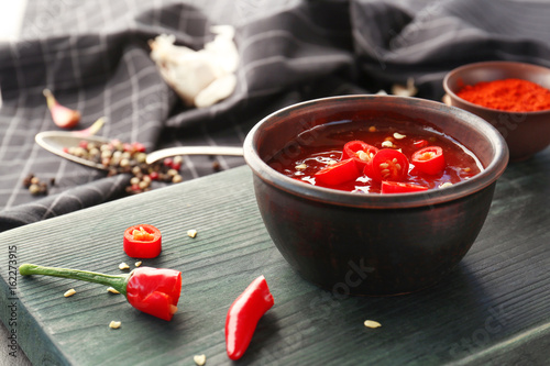 Tasty chili sauce in bowl on wooden board