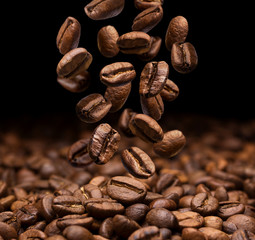 Falling coffee beans on dark background, close-up