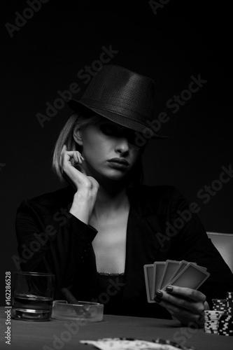 Studio shot of beautiful young woman playing poker плакат