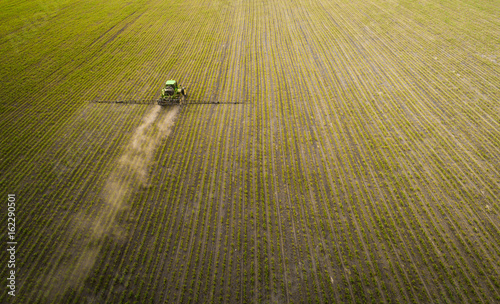 Fotobehang Trekker A blue tractor moves through the spring field and sprays fertilizers on plants planted on it. Spring processing of agricultural crops. View from above. Aerial view