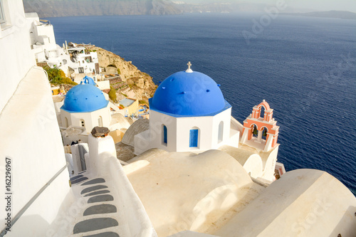 View of three blue domed churches and sea in Oia, Santorini, Greece