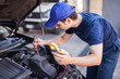 Car electrician troubleshooting a car engine