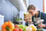 Young woman standing by the stove in the kitchen . - 162305183