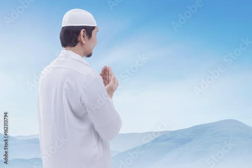 Poster Young muslim man wearing cap praying