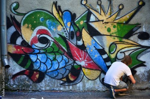 Photo of a young guy in denim shorts and a white shirt. The guy draws on the graffiti wall a drawing with aerosol paints of various colors. The concept of hooliganism and damage to property - 162333113