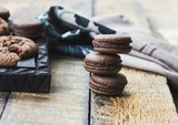 Fresh baked chocolate macarons on wooden texture with towel