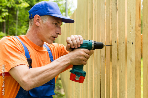 Plakat Close up portrait of worker, mounting wooden fence using electric screwdriver