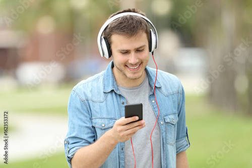 Teen boy walking and listening on line music