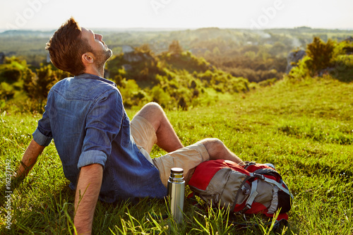 Middle-aged man relaxing and enjoying the ambience after long hike in the mountains