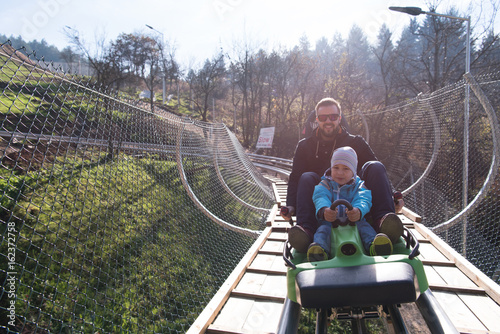 father and son enjoys driving on alpine coaster