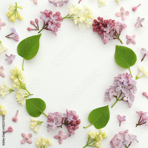 Decorative frame made of flowers and lilac leaves on a white surface. View top.
