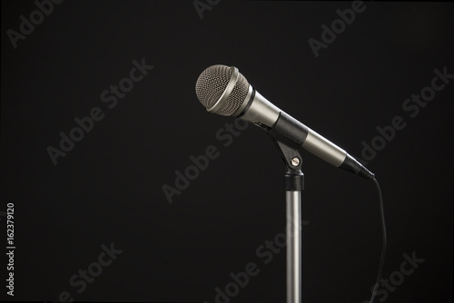 Staande foto Muziekwinkel Microphone on a stand seen from the side on a black background