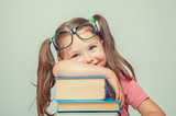 smiling beautiful cute little girl leaning on thick books - 162417722